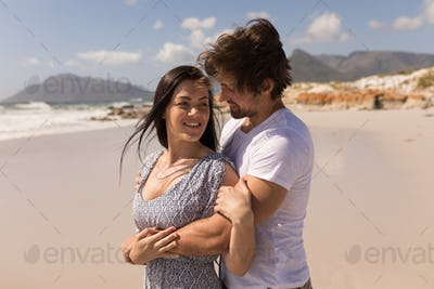 Side view of romantic happy young couple embracing on beach in the sunshine