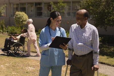 Happy young female doctor discussing medical report with senior man on clipboard in garden