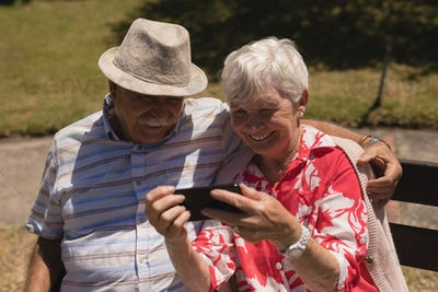 Front view of happy senior couple using mobile and sitting on bench  phone in garden