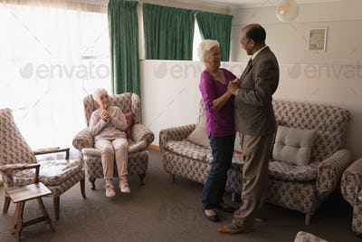 Side view of happy senior friends dancing together  with their friend sitting on the sofa at home