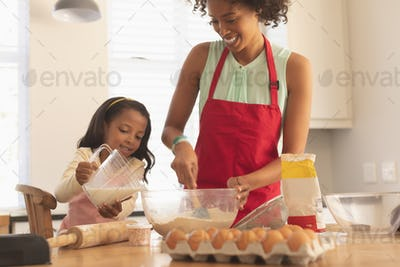 Mother and daughter mixing ingredients together in kitchen at home, they are smiling and having fun