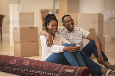 Front view of happy African American couple sitting on floor and looking away at home