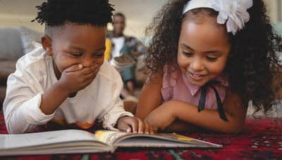 Cute African American sibling lying on floor and reading a storybook in a comfortable home