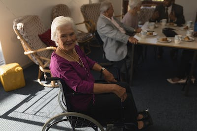 Side view of disable senior woman sitting on wheel chair and looking at camera in home