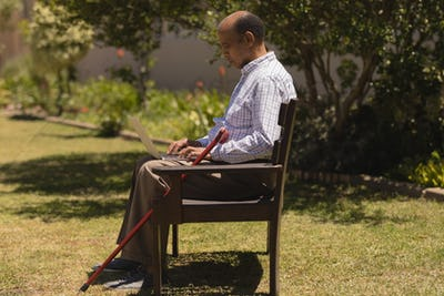 Side view of active senior man using laptop while sitting on a bench on sunny day  in the park