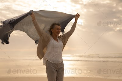 Side view of a thoughtful pretty senior Caucasian woman standing with waving shawl on the beach