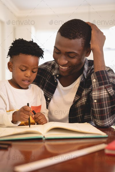 Front view of African American father helping his son with homework at table