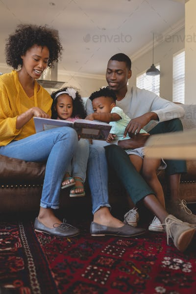 Happy parents with their cute children reading storybook on the sofa in a comfortable home