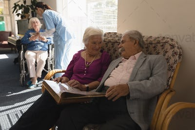 Front view of senior couple looking photo album on sofa at nursing home
