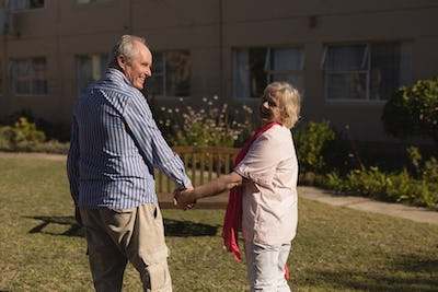 Rear view of happy Caucasian senior couple being active while holding hands in the park