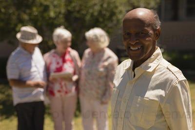 Front view of happy senior man looking at camera while senior women are standing behind in garden