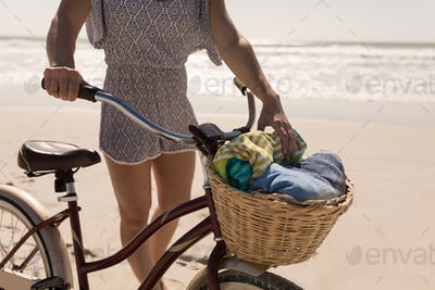 Mid section of young woman with bicycle standing on beach in the sunshine