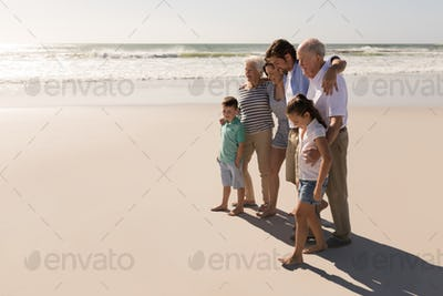 Side view of happy multi-generation family with arms around walking on beach in the sunshine