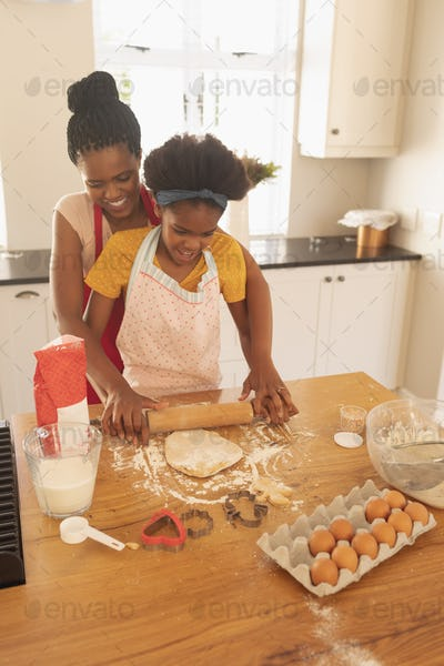 Front view of African American mother and daughter baking cookies in kitchen at home