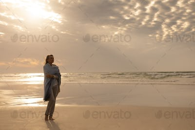 Side view of a thoughtful senior Caucasian woman wrapped in a shawl standing on the beach