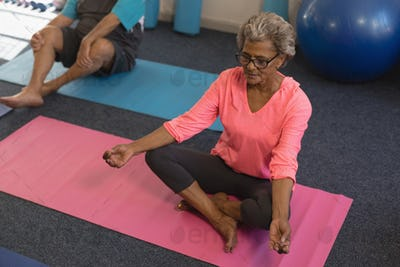 High angle view of senior woman doing yoga in yoga position in fitness studio