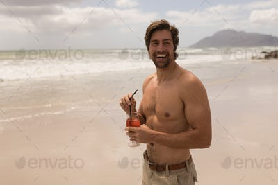 Front view of shirtless happy young man with cocktail looking at camera on beach in the sunshine