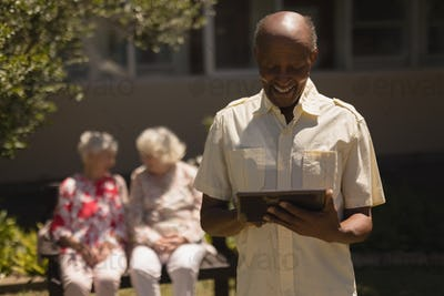Front view of happy senior man suing digital tablet with senior women on the background in garden