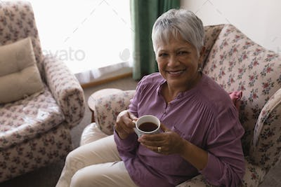 High angle view of happy senior woman having black coffee on sofa in living room at home