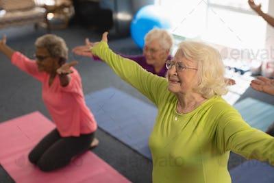 Happy senior people exercising in yoga position in fitness studio