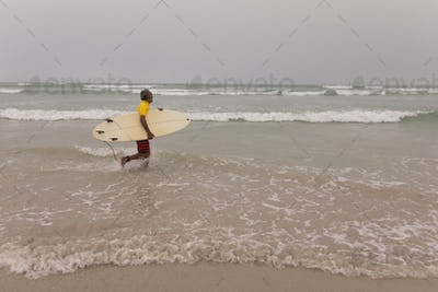 Side view of senior male surfer with surfboard running on the beach