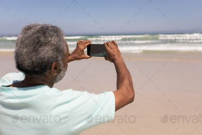 Rear view of senior man clicking photo with mobile phone on beach in the sunshine