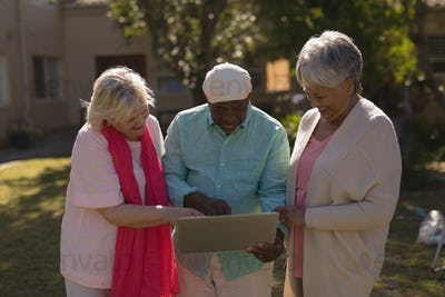 Front view of active senior African-Americans and Caucasian people using laptop in the park