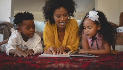 Mother with her cute children lying on floor and reading a storybook in a comfortable home