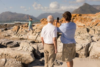 Rear view of father and son with arms around taking selfie with mobile phone on beach