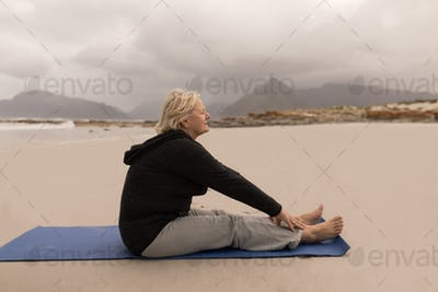 Front view of active senior woman stretching on a yoga mate on the beach
