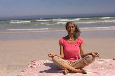 Front view of senior woman with eyes closed doing yoga on beach in the sunshine