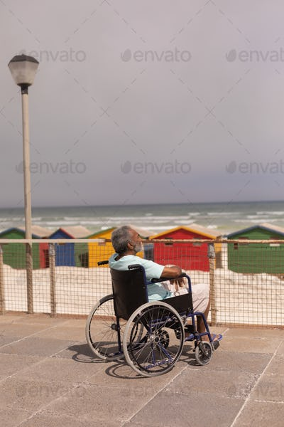 Side view of disabled senior man sitting on wheelchair at promenade in the sunshine