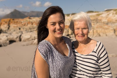 Front view of happy mother and daughter looking at camera on beach in the sunshine