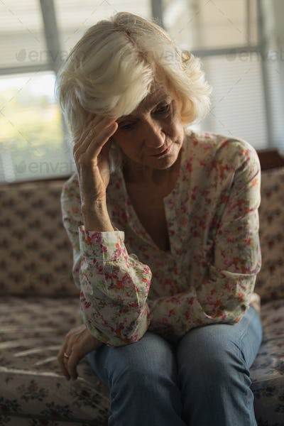Front view of worried senior woman relaxing on sofa in living room at nursing home