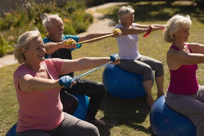Side view of group of active senior people exercising with elastic band and on ball in the park