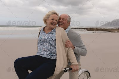 Side view of active senior man with senior woman riding bicycle on the beach