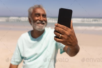 Front view of happy senior man talking selfie with mobile phone on beach in the sunshine