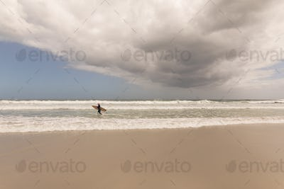 Front view of an active senior woman running with surfboard on the beach