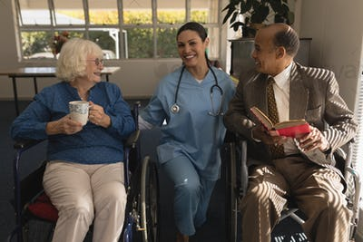 Front view of happy female doctor taking care and talking with disable senior couple at home