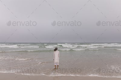 Rear view of senior woman standing at beach on a cloudy day