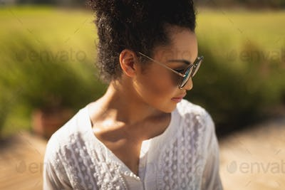 Close-up of young mixed-race woman with sunglasses standing in backyard of her home on a sunny day