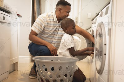 Side view of African American father and son washing clothes in washing machine at home