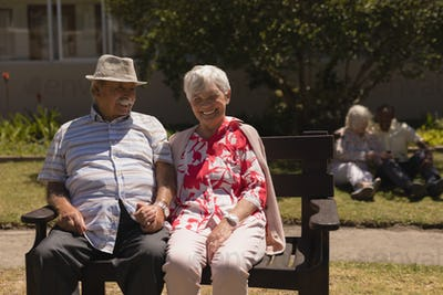 Front view of happy senior couple holding hands and sitting on bench in garden