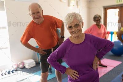 Front view of happy senior couple exercising in fitness studio