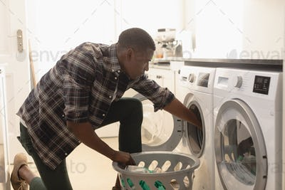 Side view of young African American man washing clothes in washing machine at home