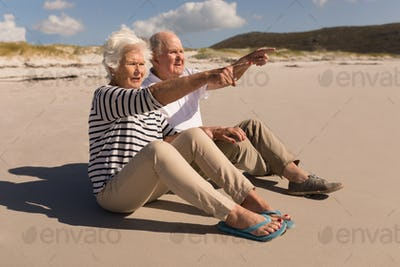 Side view of senior couple pointing at distance while sitting on beach in the sunshine
