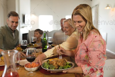 Side view of a family eating, smiling woman take food at home