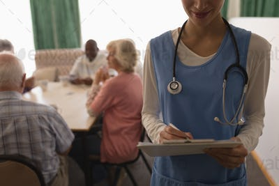 Female doctor holding clipboard and pen with senior people playing card around a table behind