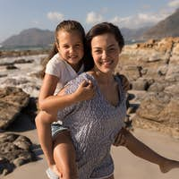 Front view of beautiful young mother giving piggyback to her daughter on beach