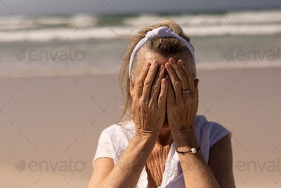 Front view of worried senior woman covering her face while standing on the beach